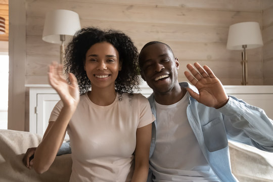 Happy african american family couple waving, sitting on sofa.