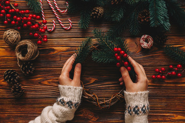 Wall Mural - Top view of process preparation for christmas. Woman wear in winter sweater making hanmade Christmas tradition whreat. Flat lay holding hands