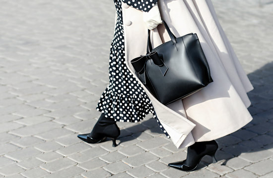 Woman in autumn or spring in a beige coat and a black dress with white polka dots. Fashionable bag close-up in female hands.Girl walks in the city outdoors. Stylish modern and feminine image, style.