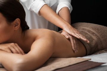 wellness, beauty and relaxation concept - beautiful young woman lying and having back massage at spa