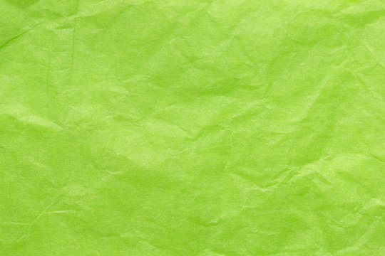 Crumpled wrapping paper in a delicate green color. Background with paper texture effect