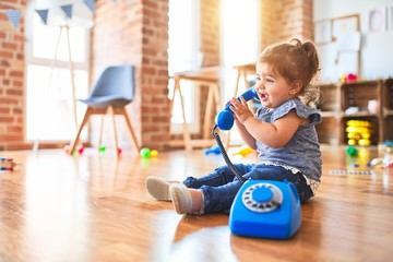 Obraz Beautiful toddler sitting on the floor playing with vintage phone at kindergarten - fototapety do salonu