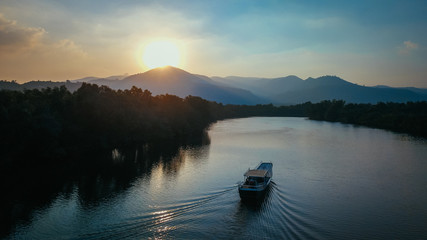 Beautiful Drone Shot of a Boat on the Prek Kampot River at Sunset during a River Cruise in Kampot, Cambodia. Wall mural