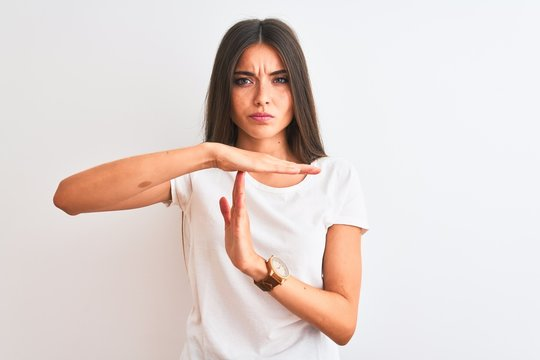 Young beautiful woman wearing casual t-shirt standing over isolated white background Doing time out gesture with hands, frustrated and serious face