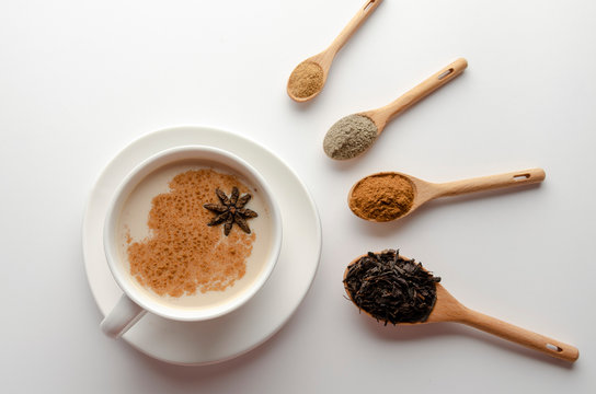 Traditional indian masala chai tea with spices - cinnamon, cardamom, anise, white background. Top view copy space