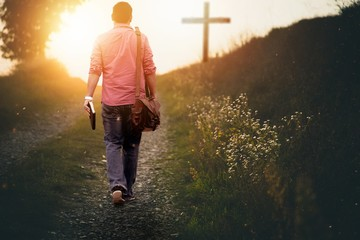 Male holding the bible walking up to the hill towards the cross with a blurred background
