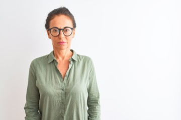 Wall Mural - Middle age woman wearing green shirt and glasses standing over isolated white background with serious expression on face. Simple and natural looking at the camera.