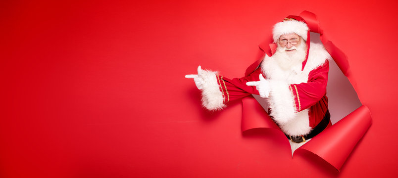 Santa Claus pointing on red empty background.