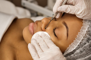 Procedure mechanical face cleaning in beauty salon. Afro american young model getting cosmetic face skin care and treatments in cosmetologist. Spa, cosmetology and wellness relaxation concept.