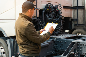 Truck driver inspecting safety daily checklist to before driving the truck
