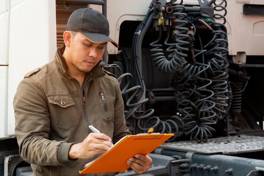 Portrait of automobile mechanic inspecting checklist program of the semi truck