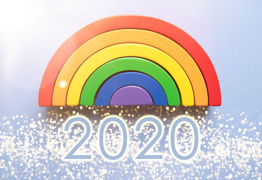 Bright rainbow toy on a blue background with bokeh glitter and 2020 in big glowing numbers - creative new year 2020 flat lay composition