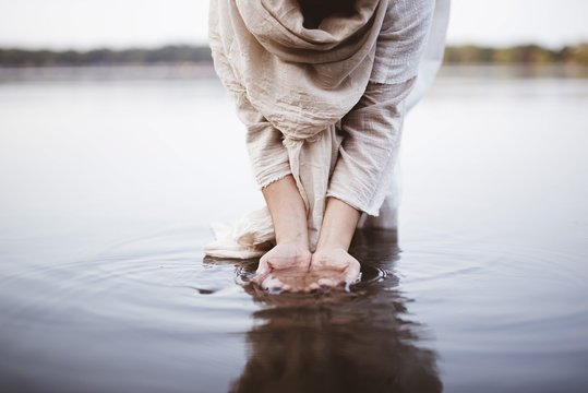 Closeup shot of a female wearing a biblical robe standing in the water while washing her hands
