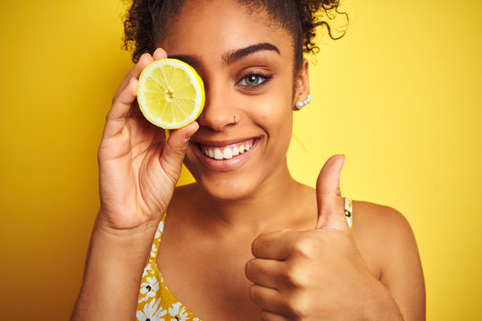 Young african american woman holding slice of lemon over isolated yellow background happy with big smile doing ok sign, thumb up with fingers, excellent sign