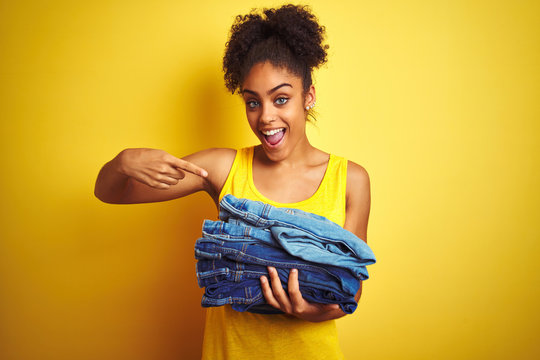Young african american woman holding stack of jeans over isolated yellow background very happy pointing with hand and finger