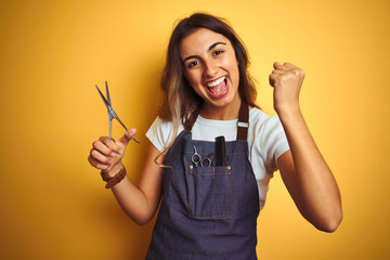 Young beautiful hairdresser woman holding scissors over yellow isolated background screaming proud and celebrating victory and success very excited, cheering emotion