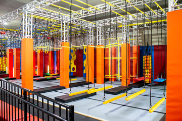 Brightly coloured interior ninja warrior parkour gym obstacle course with aerial netting