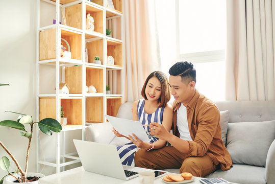 Portrait of beautiful young Asian couple using laptop on the sofa at home.