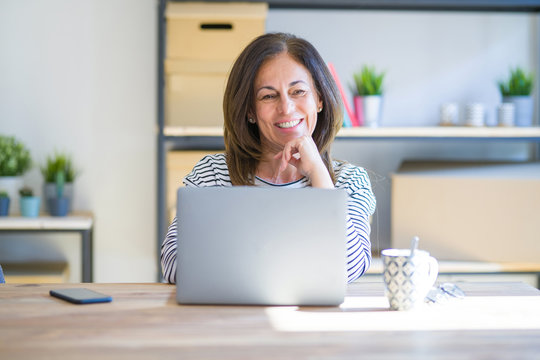Middle age senior woman sitting at the table at home working using computer laptop looking confident at the camera smiling with crossed arms and hand raised on chin. Thinking positive.