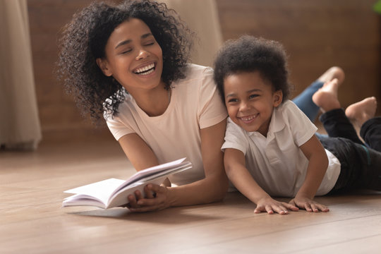 Smiling black mom and little son have fun reading