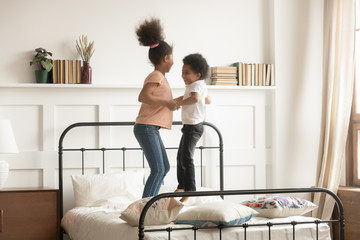 Active black brother and sister jump on bed together