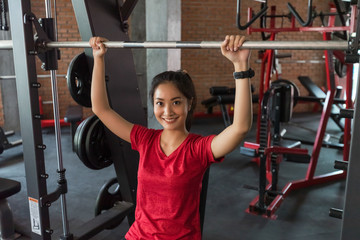 Picture cute of a smile asian woman exercising building muscles in the gym, concept of healthy lifestyle