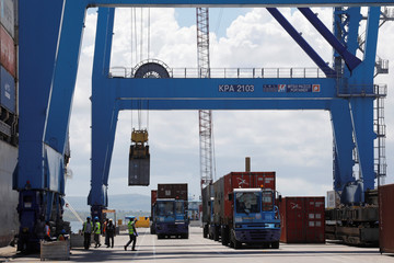A crane loads shipping containers on a ship in the port of Mombasa