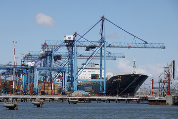 A container ship is seen as its docked next to cranes at the port of Mombasa