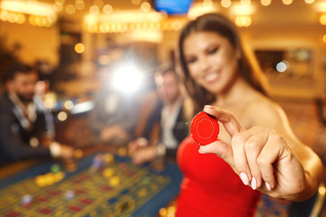 Beautiful girl holding a chip in her hand in a casino