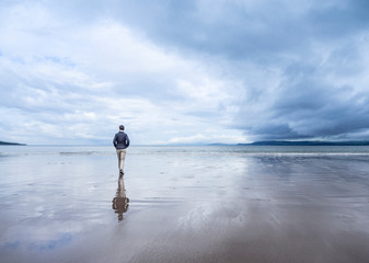 person walking along the beach with reflections