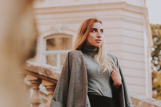 Stylish autumn fashionable girl image. Gray blazer, pleated skirt and gray coat. Blond woman/Old city background.