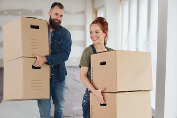 Happy young couple carrying boxes into a new home
