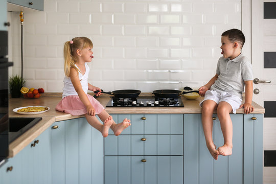 siblings children fry pancakes in the kitchen