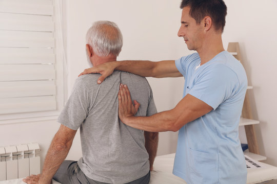 Senior man with back pain. Spine physical therapist and paient. chiropractic pain relief therapy. Age related backache