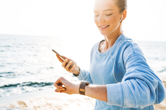 Woman running outdoors on beach looking at watch clock.