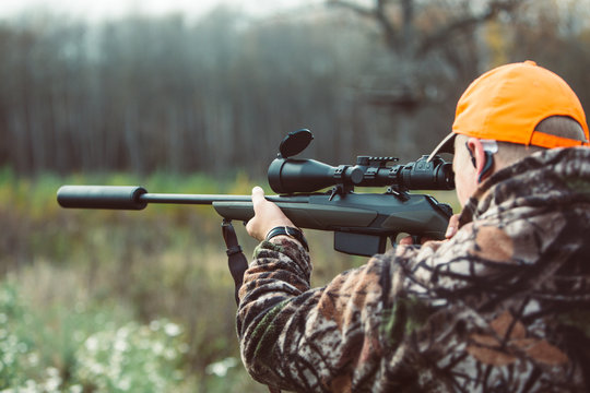 Hunter hold rifle  and aiming to deer.  Hunting optics equipment for professionals. Man aiming target. Leisure ir nature. Aiming skills.