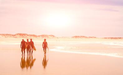 A group of surfers walks along the ocean beach. sunny