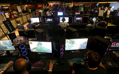 Gamers sit in front of computers screen play games as they participate during the Gaming festival in Dubai