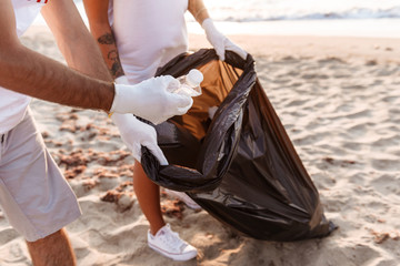 Cropped image of a volunteer group cleaning beach from rubbish