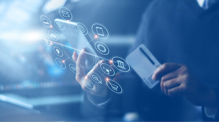 Businessman with mobile smartphone and credit card in hand paying online and shopping on virtual interface global network, online banking and digital marketing.