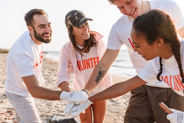 Image of smiling teamwork volunteers holding hands together