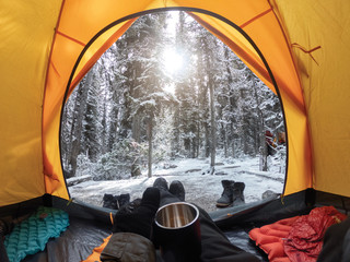 Poster Camping Camping with hand holding cup in yellow tent with snow in pine forest