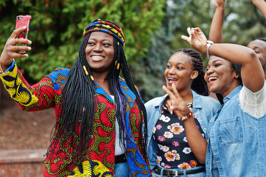 Group of five african college students spending time together on campus at university yard. Black afro friends making selfie on phone. Education theme.