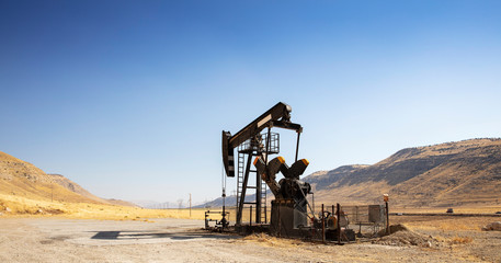 Oil drilling derricks at desert oilfield. Crude oil production from the ground. Oilfield services contractor. Oil drill rig and pump jack. Petroleum production, natural gas, liquids, NGL, additive.