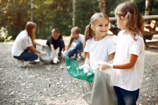 Volunteers collects rubbish. Children in a park. Kids in a white t-shirts