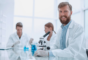 successful young scientist sitting at his Desk in the laboratory