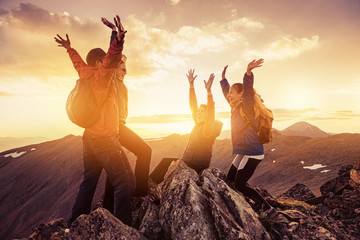 Four happy hikers on mountain top at sunset