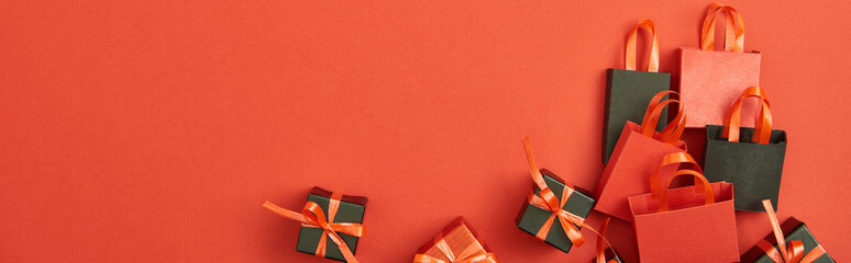 top view of gift boxes and shopping bags on red background with copy space, panoramic shot