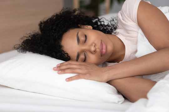 Calm african American girl sleeping on white soft pillow