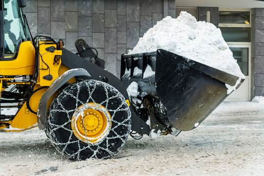 Big loader machine with steel metal chains removing big snow pile from city street at alpine mountain region in winter. Heavy snowfall aftermath. precipitation cleaning equipment